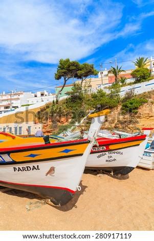 CARVOEIRO BEACH, PORTUGAL - MAY 17, 2015: colorful typical fishing boats on beach in Carvoeiro coastal village. Carvoeiro is popular holiday tourist destination on Algarve coast. - stock photo