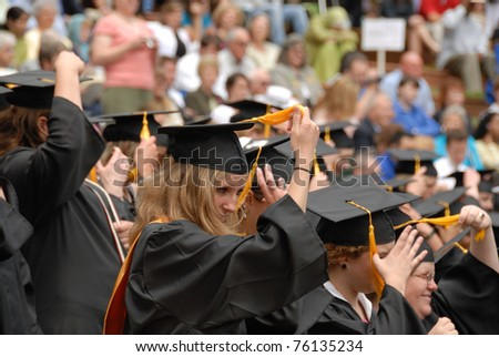 CARY, NC - MAY 15: Girls move the position of their cap tassels to mark a successful graduation at Meridith College on May 15, 2007 in Cary, NC. - stock photo