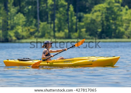 CARY, NORTH CAROLINA - MAY 28: Young woman enjoys relaxing on her Necky Rip 17 Kayak on 28 May 2016 at Lake Jordan
