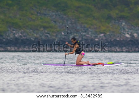 CARY, NORTH CAROLINA - SEPT 5: Stand up paddle boarder finishing a long workout on 5 Sept 2015 at Lake Jordan