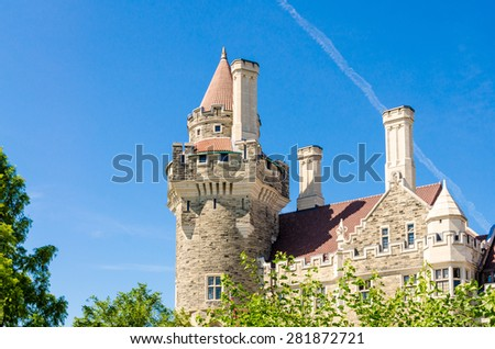 Casa Loma an example of a Medieval Castle and Gothic Revival architecture: tower hit by bright sunlight under a clear blue sky. - stock photo