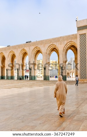 CASABLANCA, MOROCCO, APRIL 2, 2015: Local man walks on the outside grounds of Hassan II Mosque or Grande Mosquee Hassan II - stock photo