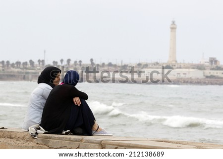 CASABLANCA, MOROCCO - JULY 23: Local people sitting at the pavement near the King Hassan II Mosque on July 23, 2014 in Casablanca, Morocco.Casablanca is the industrial center of the country. - stock photo