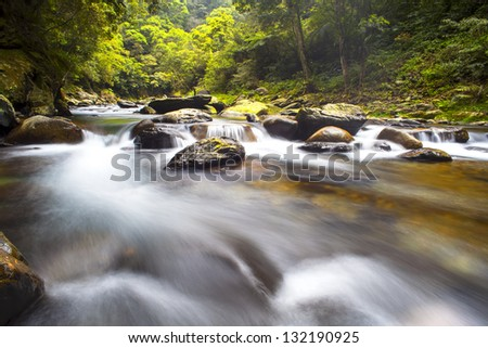 Cascade falls over mossy rocks for adv or others purpose use - stock photo