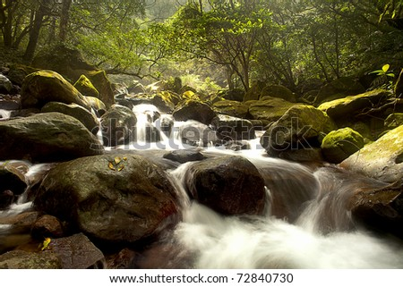 Cascade falls over old plum river with rocks - stock photo