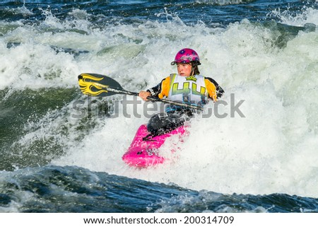 CASCADE, IDAHO/USA - JUNE 21, 2014: Number 44 pushing herself to win at the Payette River Games