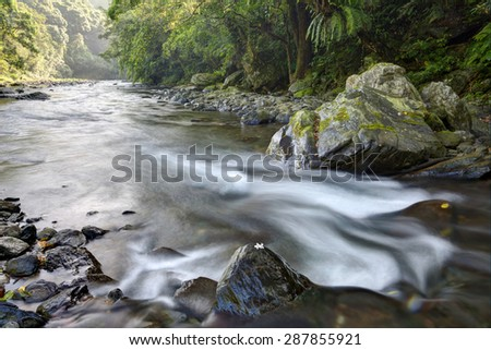 Cascade in a mysterious forest with sunlight shining through the lavish greenery  - stock photo