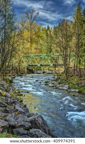 Cascade Mountain River and Bridge on Sunny Spring Afternoon - stock photo