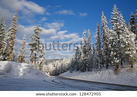 Cascade Mountains, high elevation mountain pass near Canada Border, with October snow fall on road & clear blue sky, near Loup Loup Ski Area, Pacific Northwest, Washington state - stock photo