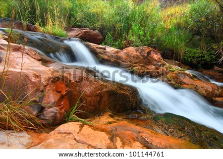 Cascades of a small stream flowing through Grand Canyon National Park on its way to the Colorado River - stock photo
