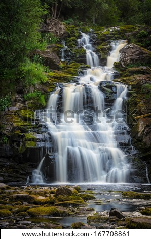 cascades of high waterfall in forest - stock photo