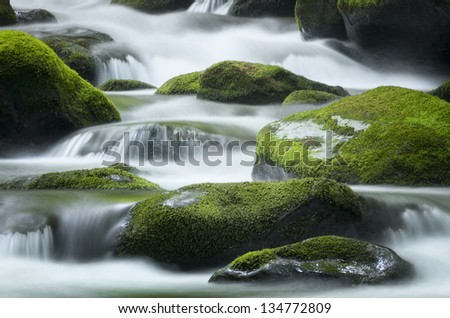 Cascading water over bright green moss-covered boulders in Tennessee - stock photo