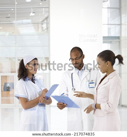 Case discussion at medical center. Doctor, nurse and patient. - stock photo