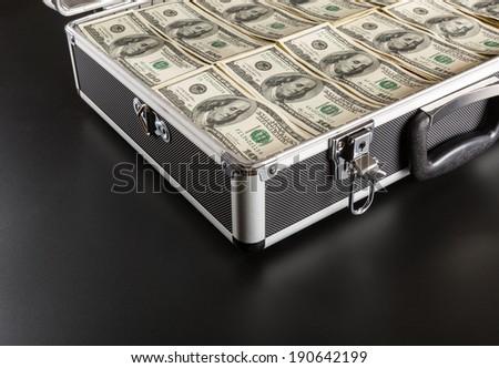 Case full of money on gray background - stock photo
