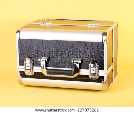 case with cosmetics on yellow background - stock photo