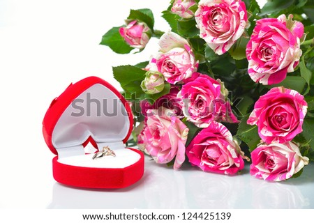 Case with the ring next to bouquet on white background - stock photo