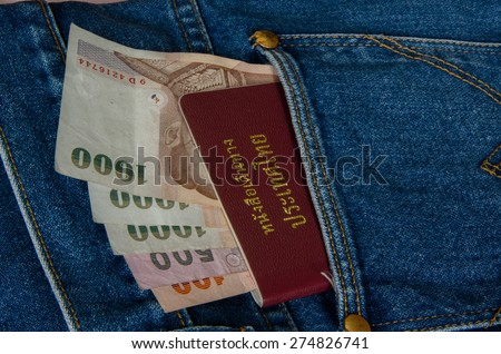 Cash and Thai passport on blue jeans pocket - stock photo