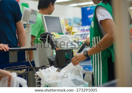 Cash desk with cashier serving customers in supermarket - stock photo