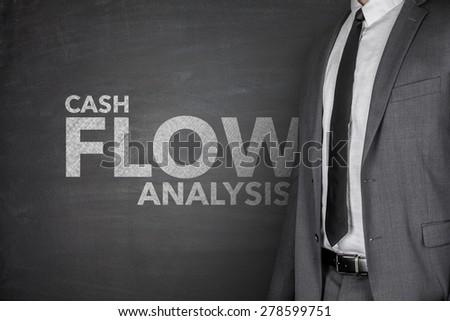 Cash flow analysis on black blackboard with businessman - stock photo
