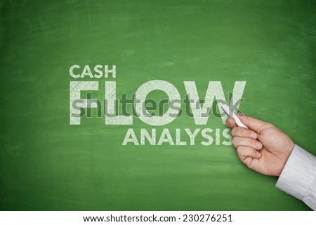 Cash flow analysis on green blackboard with dollar bills - stock photo