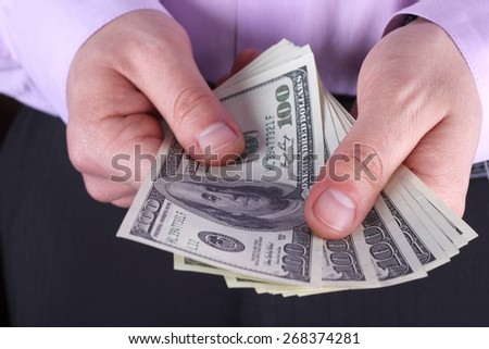 Cash in hands.  Profits, savings. Stack of dollars. Man counting money. Dollars in man's hands. A man in business clothes with dollars. Success, motivation, financial flows, wealth. Stack of dollars. - stock photo