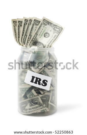 "Cash jar overflowing with US Dollar Bills. Sign with ""IRS"" is taped to the jar. Studio shot isolated on white background, saved with clipping path"