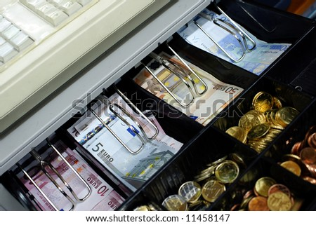 Cash machine with euro banknotes and coins .