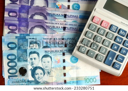 Cash money and a calculator Photo of a bunch of cash money and a calculator - stock photo