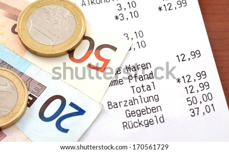 Cash receipt on a brown table Note for inspector: No personal information given, only cash receipt and the amounts - stock photo