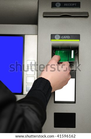 Cash withdrawal. Woman's hand inserting plastic card Visa into the ATM - stock photo