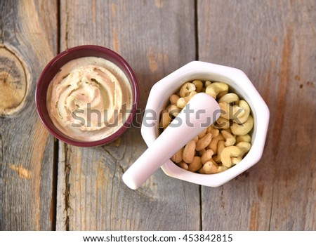 Cashew butter with raw cashews and mortar and pestle - stock photo