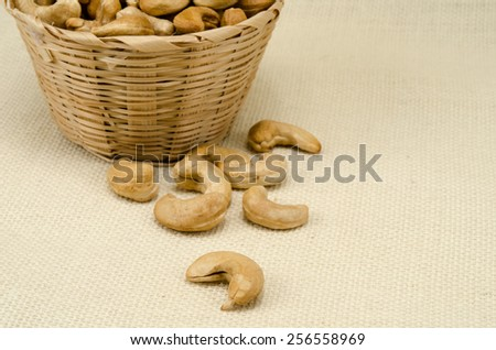 Cashew nuts in bamboo woven on sack background - stock photo