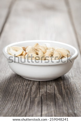 Cashew nuts in white bowl on wooden table. - stock photo