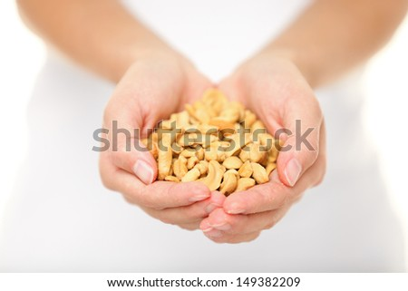 Cashew nuts - woman showing salty cashew nuts handful. Healthy food snack and ingredient shot in studio with shallow depth of field.