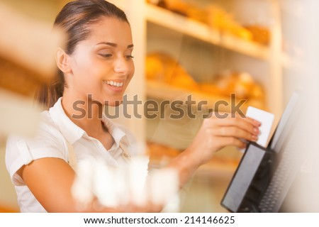 Cashier at work. Attractive young female cashier swipes a plastic card through a machine and smiling - stock photo