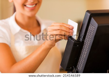 Cashier at work. Close-up of beautiful young female cashier swipes a plastic card through a machine  - stock photo