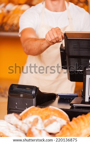 Cashier at work. Close-up of male cashier swipes a plastic card through a machine while standing in bakery shop - stock photo