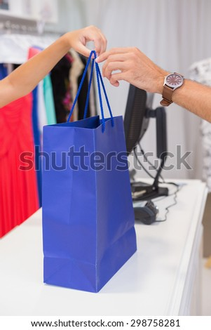 Cashier giving customer a blue shopping bag at a boutique - stock photo