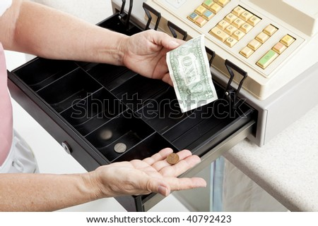 Cashier with nearly empty cash register.  Metaphor for recession. - stock photo