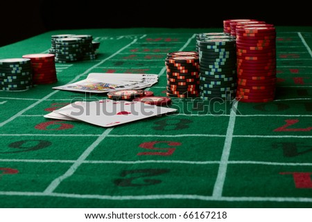Casino card game showing chips on green cloth background - stock photo