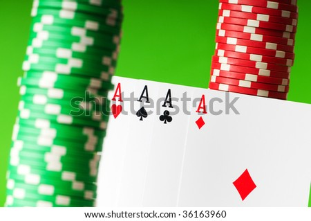 Casino chips and aces against green background - stock photo