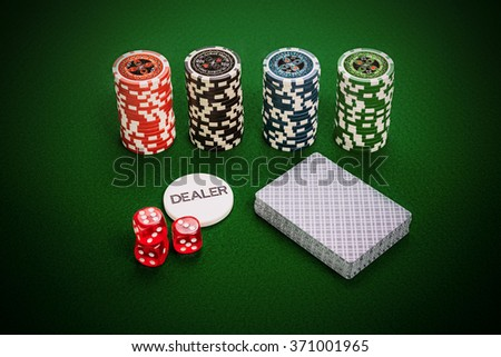 Casino chips, deck of cards, dealer chip and red casino dices lying on green casino table.