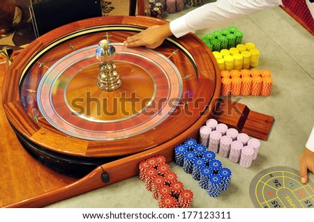 casino dealer fingers holding the ball and prepare for launching - stock photo