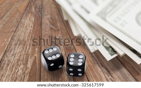 casino, gambling and fortune concept - close up of black dice and dollar cash money on wooden table - stock photo