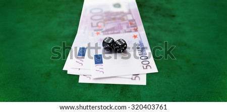 casino, gambling and fortune concept - close up of black dice and euro cash money over green felt surface background - stock photo