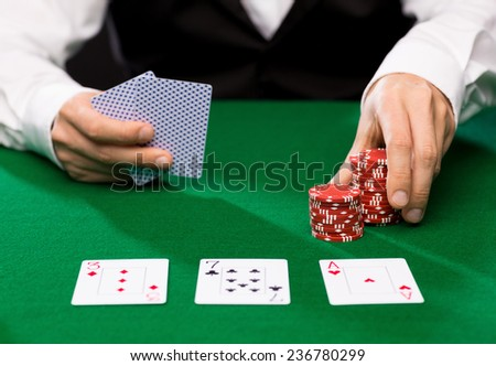 casino, gambling, poker, people and entertainment concept - close up of holdem dealer with playing cards and chips on green table
