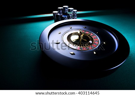 casino theme, high contrast image of casino roulette and playing chips on green canvas - stock photo