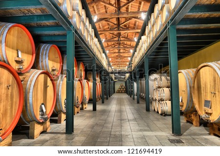 Casks in wine cellar and bottle - stock photo