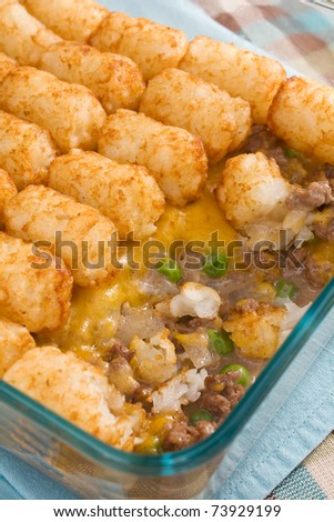 Casserole made of tater tots, cheddar cheese, ground beef, peas, and onions.