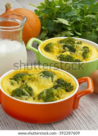 casserole with broccoli and cheese on wooden table